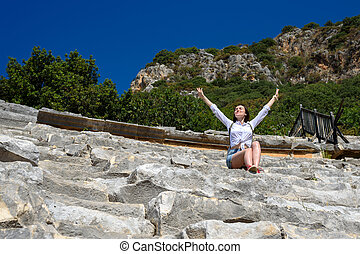 Young happy woman sitting on the rocks in the amphitheater with her hands open, smiling at the sun, freedom, relaxation, enjoyment, copy space
