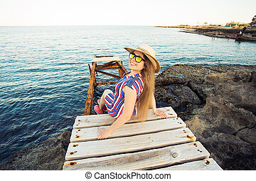 Young happy woman sitting on wooden pier and laughing.