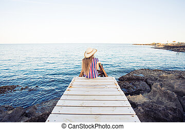 Young happy woman sitting on wooden pier, rear view.