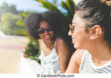 Young happy woman sitting outside with friend smiling