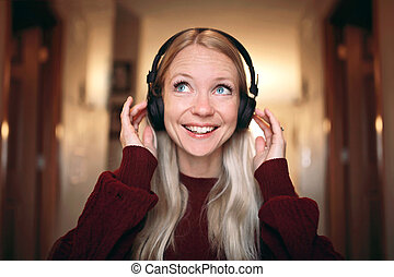 Young, Happy Woman Smiling as she Listens to Music on Wireless Headphones at Home