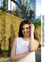 Young happy woman standing near fence