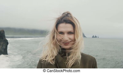 Young happy woman standing on black beach, near the troll...