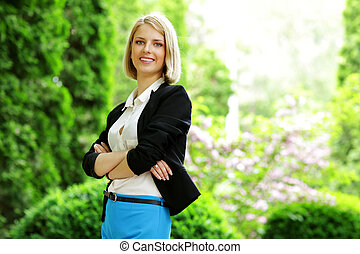 Young happy woman standing with arms folded in park