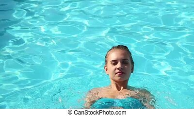 young happy woman swimming in a swimming pool