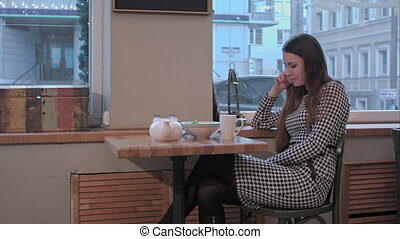 Young happy woman talking on mobile phone with friend while sitting alone in coffee shop interior
