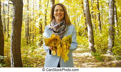 Young happy Woman Throwing Autumn Leaves in a park