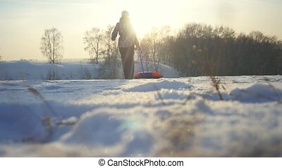 Young happy woman tobogganing running on the mountains through the sun in slow motion in winter. 1920x1080