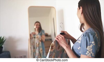 Young happy woman trying on new dress to wear in front of the mirror at home