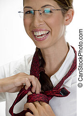 young happy woman tying her tie against white background