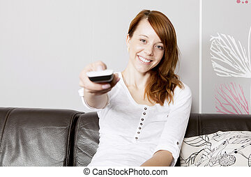 Young happy woman using a remote control