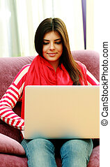 Young happy woman using laptop at home