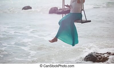 Young happy woman using mobile phone on a swing on a tropical beach and waves splashes in the sea. 1920x1080