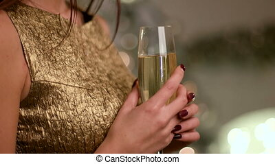 Young happy woman waiting for her boyfriend with a glass of champagne on New Year Eve.