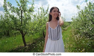 Young happy woman walking around blooming orchard