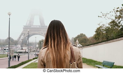 Young happy woman walking in downtown of Paris, France near...