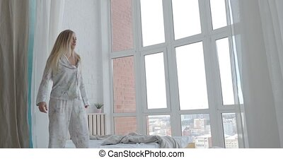 Young, happy woman wearing pajamas dancing, jumping on bed in her bedroom at home.