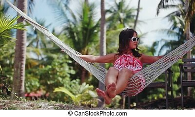 Young happy woman wearing sunglasses laying at hammock...