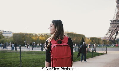 Young happy woman with backpack walking alone near the...