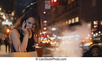 Young happy woman with bags standing in traffic downtown in the evening and talking on mobile phone in new York, America
