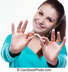 Young happy woman with broken cigarette. Stop smoking concept.