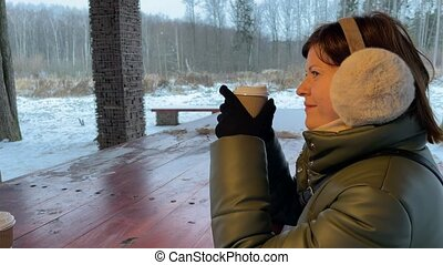 Young happy woman with coffee at cold winter time. Slow motion footage.