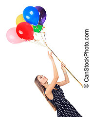 Oblique portrait of beautiful young happy woman in polka dot dress with colorful balloons isolated on white background