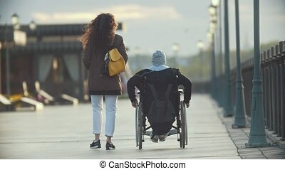 Young happy woman with disabled man in a wheelchair walking together on the quay
