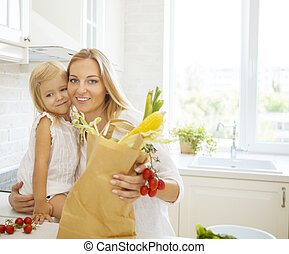 Young happy woman with her daughter cooking together