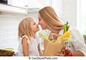 Young happy woman with her daughter cooking