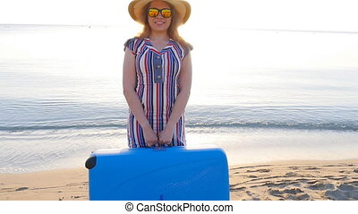 Young happy woman with large suitcase on beach