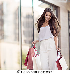 Young happy woman with shopping bags walking on street.