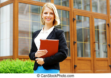 Young happy woman with tablet computer standing outdoors