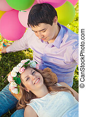 Young healthy beauty pregnant woman with her husband and balloon