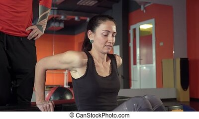 Young healthy sporty active shape girl with a handsome helpful personal trainer next to her in the gym. Sport activity