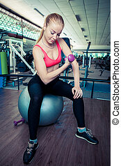 Young healthy woman do physical exercises with dumbbells on fit-ball in gym