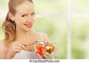 young healthy woman eats vegetable salad