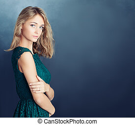 Young healthy woman fashion model on blue background with copy space