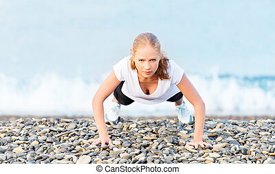 Young healthy woman playing sports push-ups outdoors on the beach, facing the sea