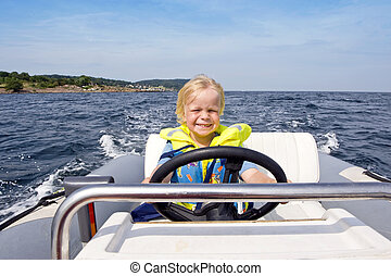 Young helmsman - Young boy behind the steering wheel of an...