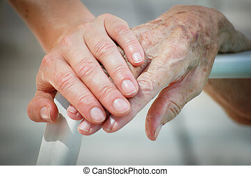 Young help Old - Young and old hand on a backrest