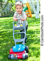Happy little boy with lawn mower in the garden