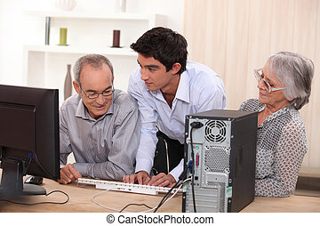 Young helping senior with computer