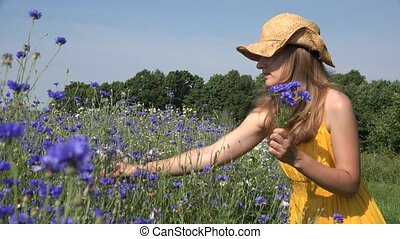 Young herbalist woman gather blue flowers and smell bouquet. 4K