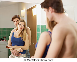 young heterosexual couple in bathroom - husband hugging wife...