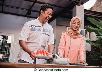 young hijab woman and boyfriend prepare cuisine breaking fast to friends