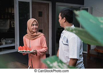 young hijab woman and young man prepare cuisine breaking fast to friends