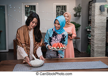 young hijab woman prepare cuisine breaking fast to friends