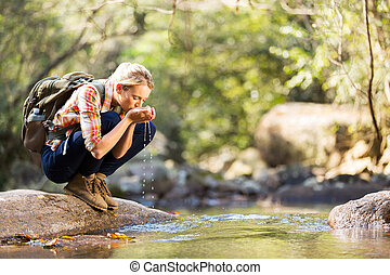 young hiker drinking stream water