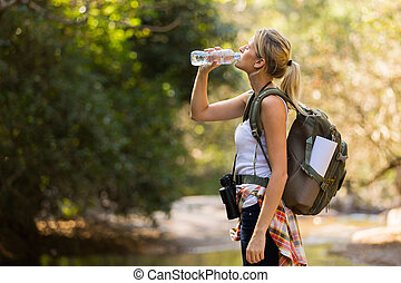 young hiker drinking water at mountain valley